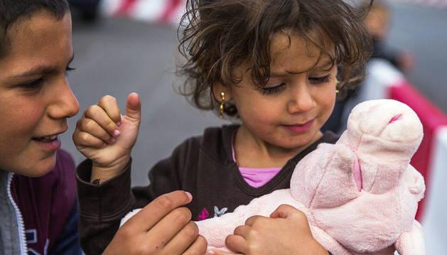 Una niña siria de tres años juega con su nuevo peluche en el puerto de Rostock en Alemania.