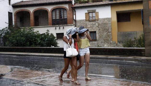 Tres jóvenes se intentran proteger de la lluvia en Pamplona.