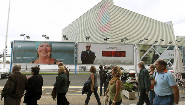 Varias personas pasan ante los carteles del Festival Internacional de Cine de San Sebastián.