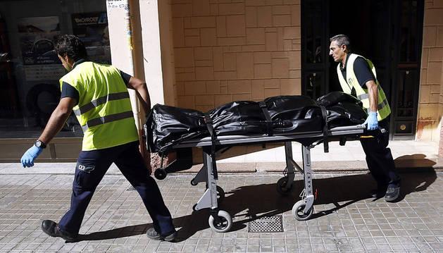 Dos operarios fúnebres retiran el cuerpo de la mujer.