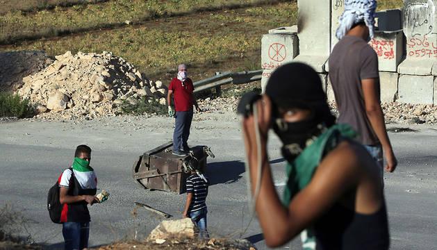 Jóvenes palestinos lanzan piedras cerca de la localidad de Betunia.