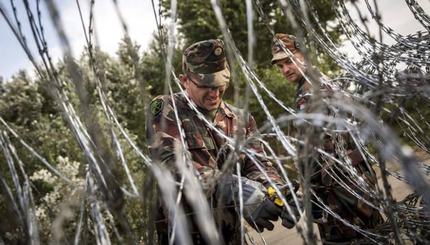 Soldados húngaros revisan la valla en la frontera de Serbia con Hungría.