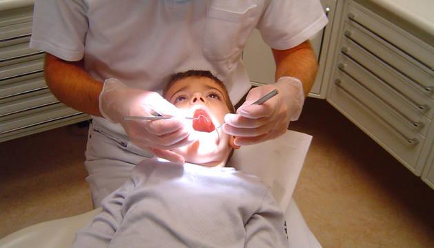 Un niño es atendido en la consulta de un dentista.