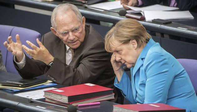 Angela Merkel conversa con el ministro de Finanzas Wolfgang Schäuble.