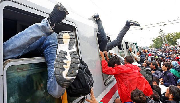 Decenas de refugiados intentan subirse a los trenes en la frontera de Hungría.