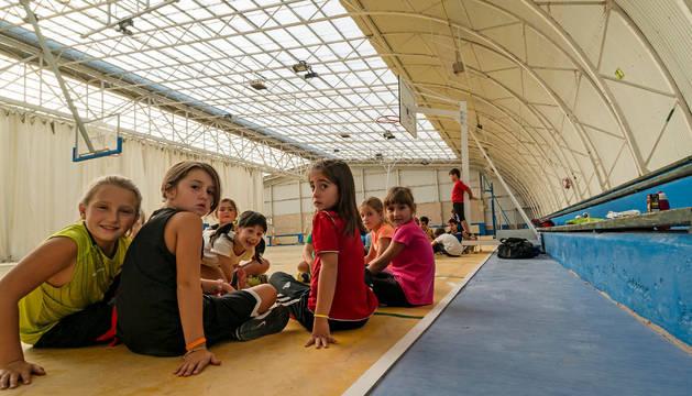 Un grupo de niñas del Club Baloncesto Oncineda sobre la pista, un poco más alta que el sintasol de color azul colocado en el pasillo.