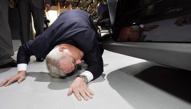 El presidente de Volkswagen AG, Martin Winterkorn, mientras se agacha para ver los bajos de un Porche GT2 durante la presentación a los medios del Salón del Automóvil de Ginebra.