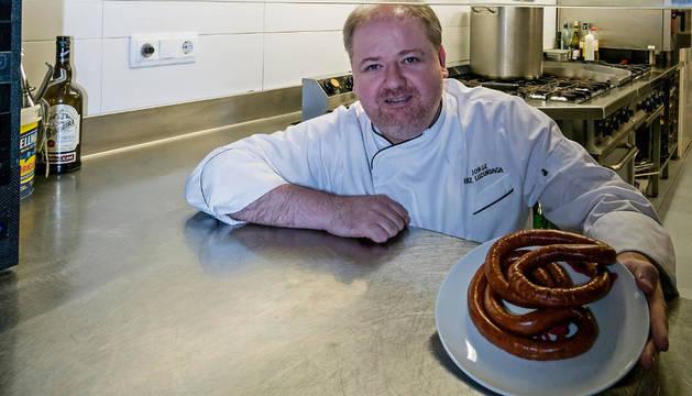 Jorge Ruiz Luzuriaga, dentro de su cocina del Bar Florida, sujeta un plato con chistorra.