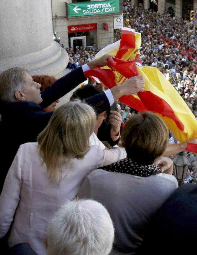 lberto Fernández Díaz intenta sacar al balcón una bandera de España.