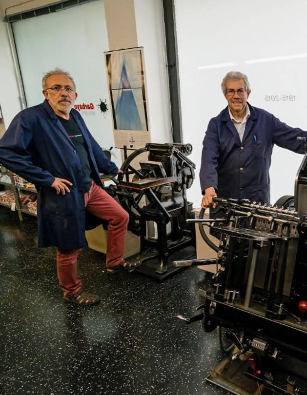Vicente Garbayo Erviti y José Ángel Garbayo posan con las máquinas de impresión.