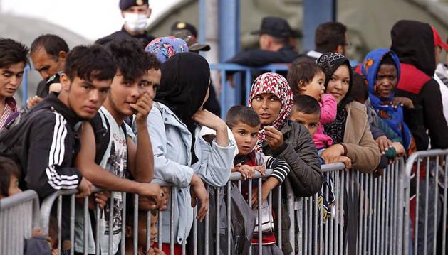Varias personas esperan en un campo de refugiados cerca de la frontera con Serbia, en Opatovac, Croacia.