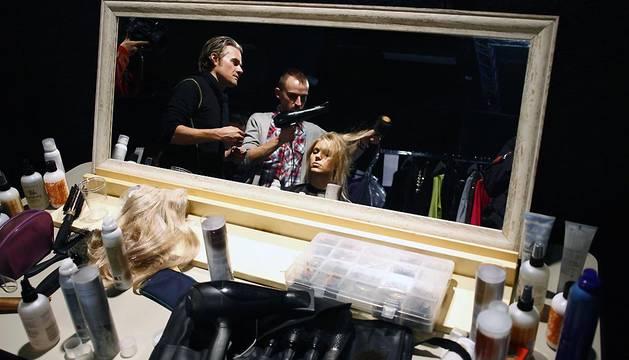 Peluqueros peinan a una modelo en la Pasarela de Milán de 2008.