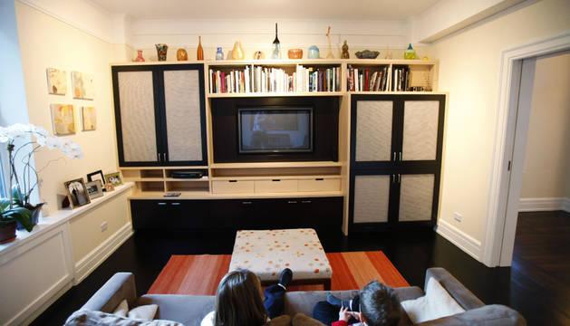 Dos niños ven la televisión en el sofá de su casa