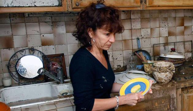 Una mujer limpiando una cocina.