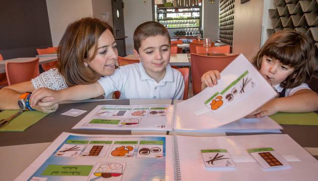 Amaya Áriz, con Mario y Leyre Navarcorena consultando un menú con pictogramas en Deboca.