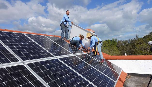 Varias personas colocan unas placas solares.