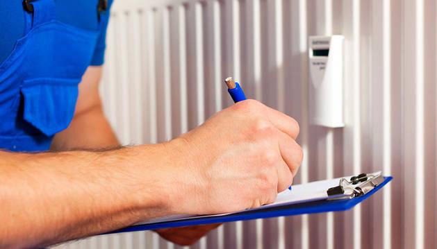 Una persona controla el consumo realizado por el radiador de una estancia de un piso