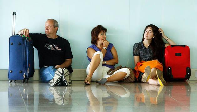 Varios pasajeros esperan sentados en un aeropuerto por el retraso de su avión.