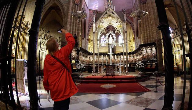 Una mujer retrataba el sábado el altar mayor de la catedral de Pamplona.