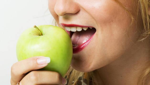Mujer comiendo una manzana.