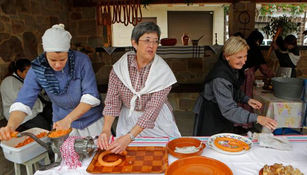 Varias mujeres elaboran la txistorra ante la mirada de los visitantes.