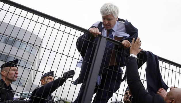 Un directivo de Air France huye saltando la valla.