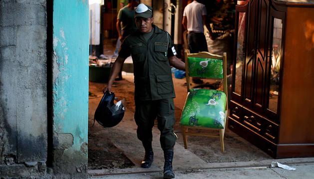 Un soldado saca una silla de una vivienda afectada por el alud.