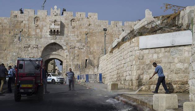 Un palestino limpia el lugar donde ha fallecido el palestino en la Puerta de los Leones en Jerusalén.