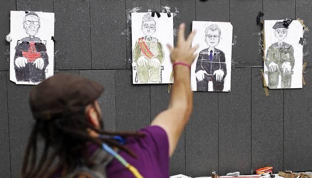 Un participante lanza su zapato a carteles con dibujos de altos cargos nacionales y mundiales, durante la 'Martxa de los pueblos Libres'.