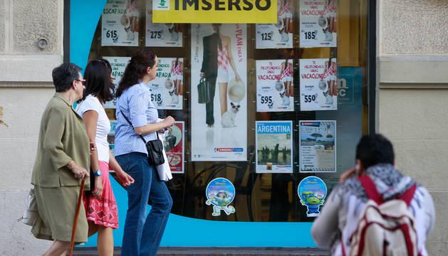Varias personas pasan ayer delante de una agencia de Pamplonaque anuncia viajes del Imserso.