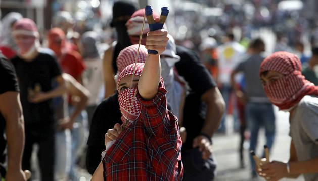Jóvenes palestinos lanzan piedras en la ciudad de Belén.