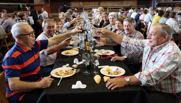 Asistentes al día del socio de los jubilados de Ribaforada brindan durante la comida.