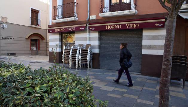 Una mujer pasa ante el Horno Viejo de la calle Herrerías de Tudela, cerrado.