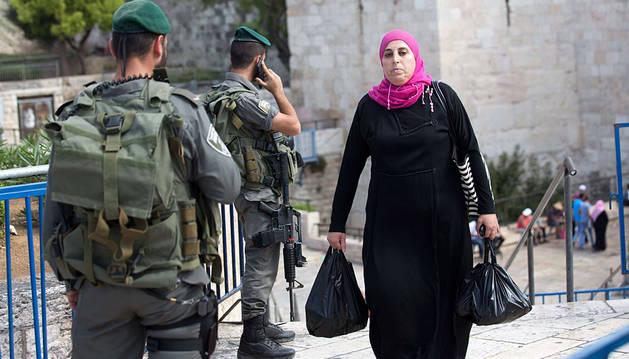 Una mujer palestina camina junto a soldados israelíes a la entrada de la Ciudad vieja de Jerusalén.