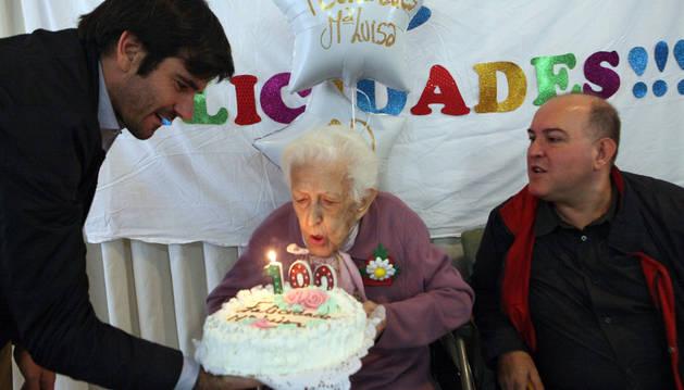 La centenaria sopla las velas junto a Eneko Larrarte -a la izda.- y Esteban Luis Rodríguez.