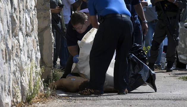 Trabajadores de una funeraria proceden al traslado del cadáver de un joven palestino que fue abatido por la policía israelí tras un intento frustrado de apuñalamiento en el barrio judío de Armón Hanatziv, en Jerusalén Este.