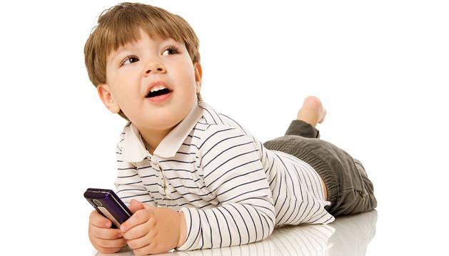 Un niño, con un teléfono móvil.