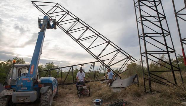 Varios operarios levantan las torres metálicas que servirán para sostener al Toro de Osborne de Tudela.