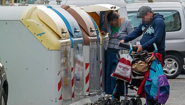 Dos personas buscan entre la basura en una localidad navarra.