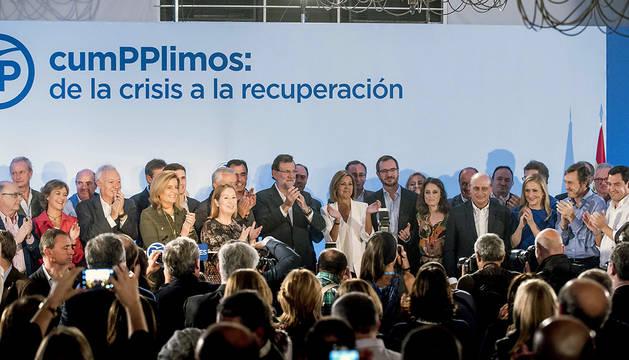Mariano Rajoy (c), rodeado por los miembros de su Gobierno, recibe los aplausos de los asistentes al acto 'CumPPlimos: De la crisis a la recuperación'.
