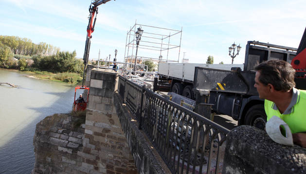 Un operario desciende pendido de una grúa hasta uno de los tajamares del puente del Ebro.