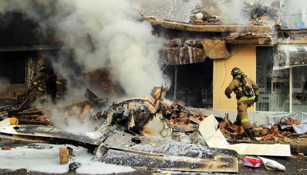 Bomberos apagando el incendio ocasionado tras accidentarse un avión bimotor en Bogotá.