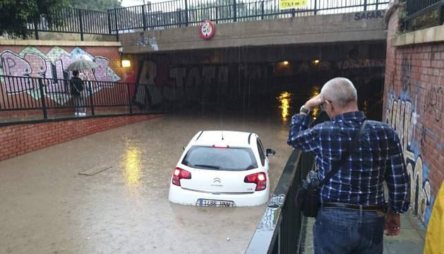 Un vehículo queda atrapado por el agua a la entrada de un puente en la capital almeriense.