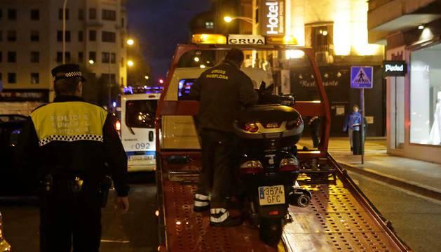 Agentes de Policía Municipal de Pamplona y operarios de la grúa retiran la moto accidentada.