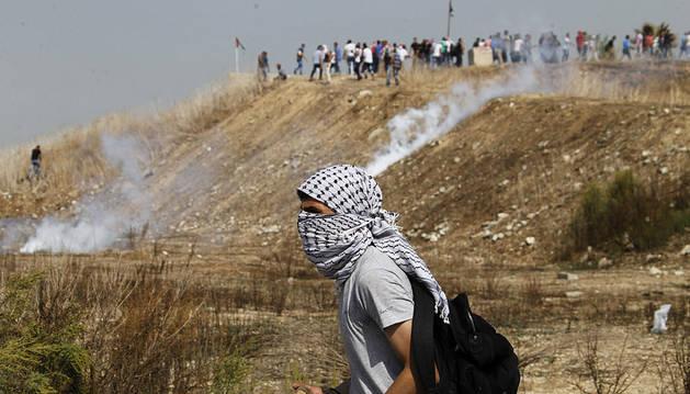 Un palestino se protege del gas lacrimógeno durante los enfrentamientos en la ciudad cisjordana de Tulkarem.