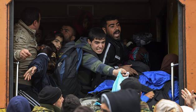 Varios refugiados se dirigen a sus familiares desde el interior de un tren.