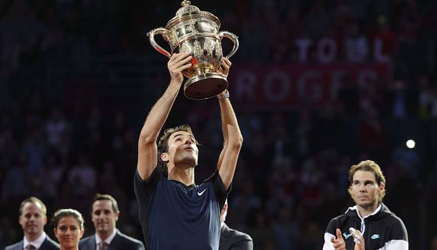 Federer levanta el trofeo ante la mirada de Nadal.