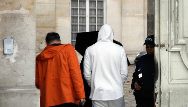 Benzema, con un jersey blanco con capucha, a la entrada de la estación de policía de Versalles, en Francia.