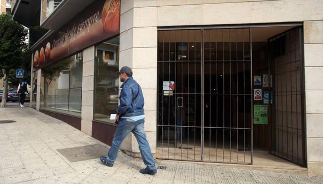 Un vecino pasa ante la fachada de la cafetería de Horno Viejo situada en la calle Fernández Portolés de Tudela.