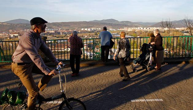 Varias personas pasean por el parque de la Media Luna en Pamplona.